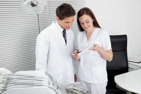 oral communication: Male dentist with assistant discussing dental report in clinic Stock Photo