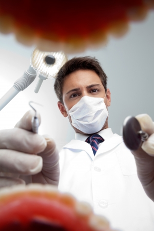 Portrait of young male dentist wearing surgical mask while examining patient s mouth photo