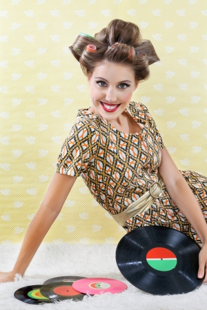hair curler: Portrait of young woman in a patterned dress wearing hair curlers while sitting with vinyl record