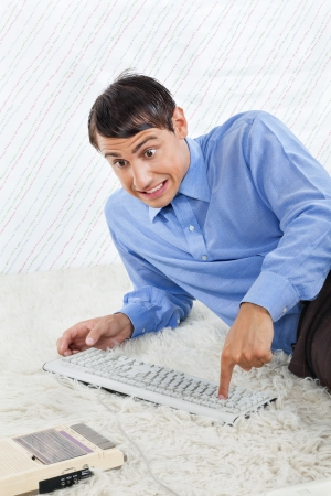 Geek businessman lying on rug with computer keyboard and vintage cassette player photo