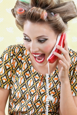 Young woman with hair curlers screaming out while holding a telephone photo