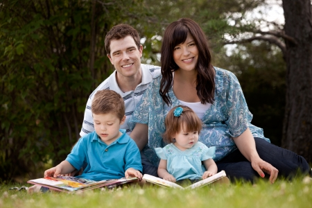 Happy young family with pregnant mother sitting and reading in park Stock Photo - 15380817