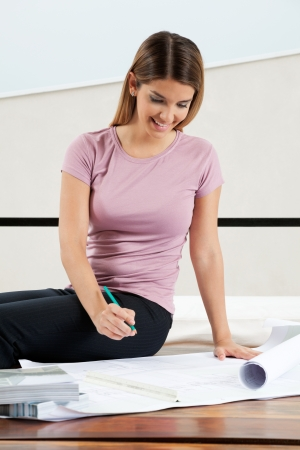 Young pretty female architect in casuals looking down at blueprint Stock Photo - 15526937
