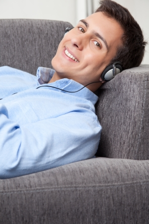 Relaxed young man on couch listening music Stock Photo - 15380842