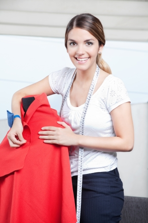 Female dressmaker adjusting clothes on tailoring mannequin Stock Photo - 15528087