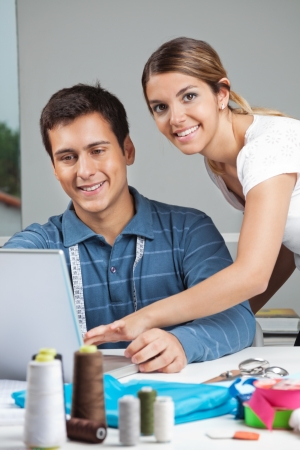 Portrait of young female fashion designer assisting man while working on laptop photo