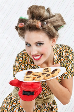 Portrait of pretty young woman with hair curlers holding plate of baked cookies Stock Photo - 15396159