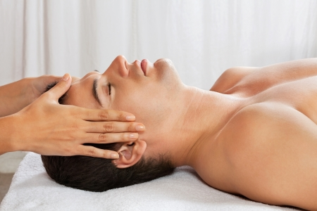 Side view of young man receiving head massage at health spa photo