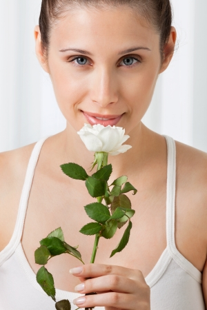 Portrait of beautiful young woman holding white rose over plain background Stock Photo - 15395934