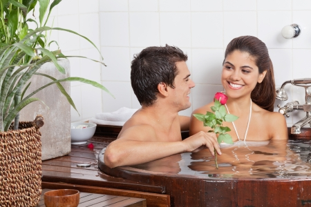 幸せな多民族若いカップルのスパでバスタブでリラックス