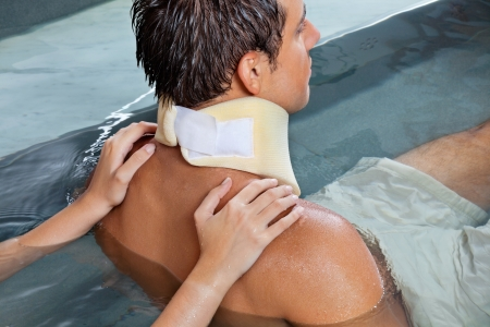 Young man wearing neck brace being massaged by female while sitting in pool photo
