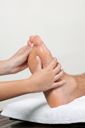 Close up of female masseuse massaging man s foot photo