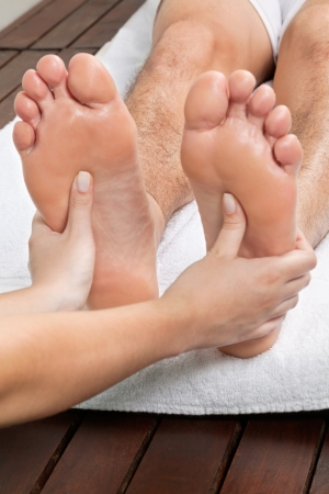 Close up of female masseuse giving foot massage to male s bare foot photo