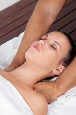 Pretty young female relaxing with eyes closed as she receives massage at health spa photo
