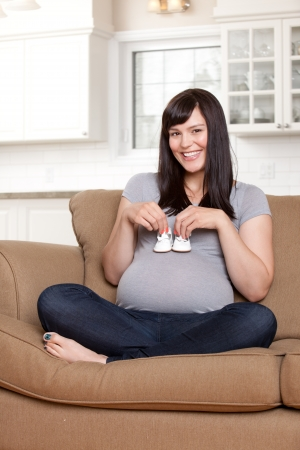 Portrait of a beautiful young pregnant woman holding baby shoes Stock Photo - 15396065