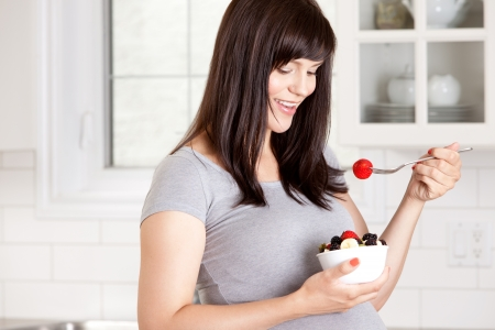 Happy pregnant woman eating healthy bowl of fresh fruit Stock Photo - 15395851