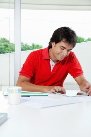 Youngman in casual t-shirt using digital tablet while sitting at desk photo