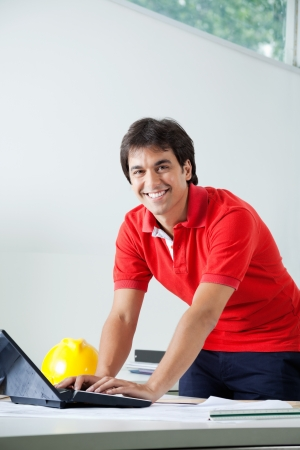 construction draftsman: Portrait of young male architect in casual wear smiling while working on laptop Stock Photo