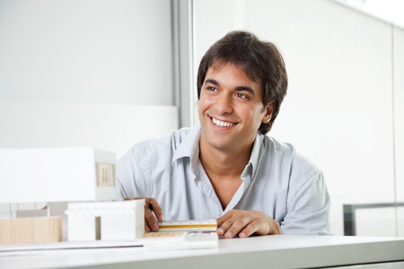 Happy young male architect looking away while creating a model house photo
