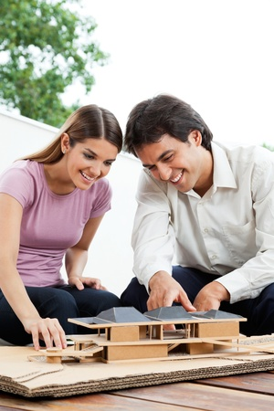 Happy young architects working on a wooden model house together photo