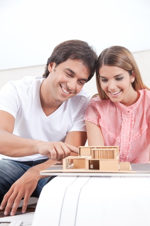tangible: Happy young couple looking at house model