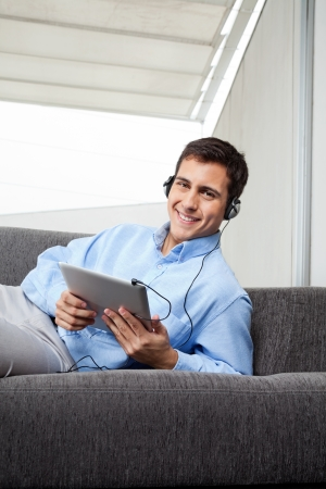 Portrait of happy young man in formal wear listening to music on digital tablet photo