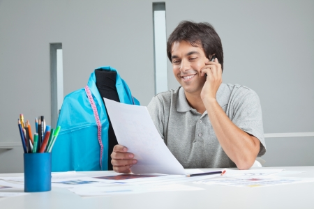 Young male clothing designer answering a phone call while holding paper photo