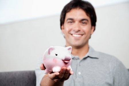 Happy young man holding piggy bank  photo
