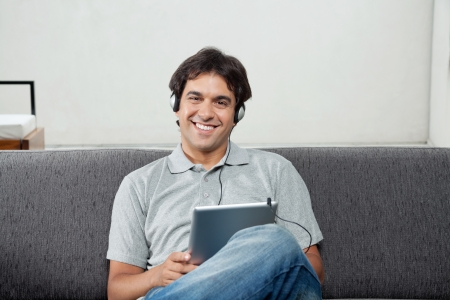 man holding book: Portrait of happy young man in casual wear listening music on tablet PC Stock Photo