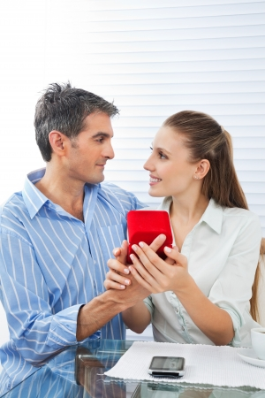Middle aged man making proposal of marriage to beautiful woman while sitting at table Stock Photo - 15396002