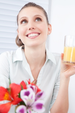 Young woman holding glass of juice, dreaming  photo
