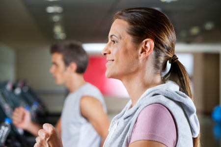 Side view of mature woman and man running on treadmill in health club photo