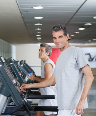 age forty: Happy men running on treadmill in fitness center