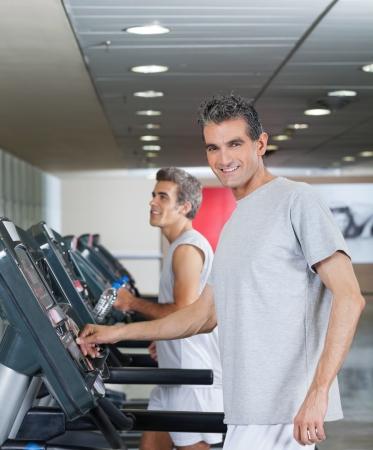 edad media: Hombres felices que se ejecutan en cinta rodante en gimnasio Foto de archivo