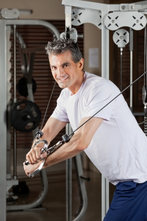 Portrait of happy mature man working out in fitness center Stock Photo - 15450056