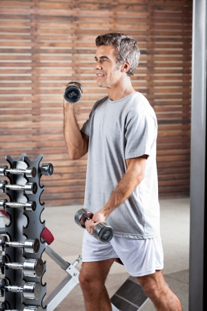 Young man lifting dumbbells in health center Stock Photo - 15450059