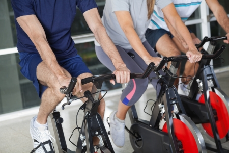Low section of men and woman on exercise bikes in health club photo