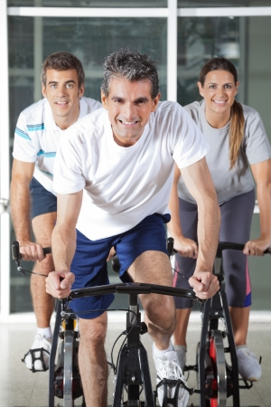 Happy men and woman on spinning bikes in health club photo