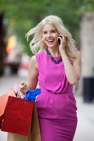 sidewalk talk: Cheerful young woman in pink dress with shopping bags using cell phone