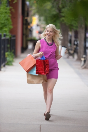 Pretty young woman with shopping bags and disposable coffee cup as she walks on sidewalk photo