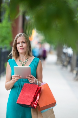 Portrait of a pretty young woman with shopping bags and digital tablet on sidewalk Stock Photo - 15449966