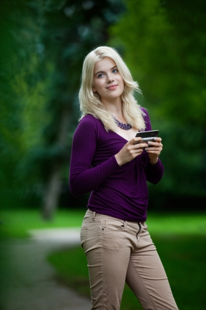 Woman looking over shoulder while using cell phone in park Stock Photo - 15450083
