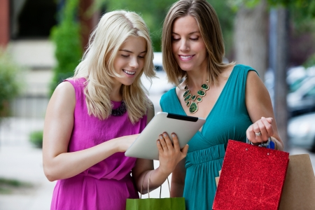 Shopping Women using Digital Tablet, outdoors  Stock Photo - 15450084