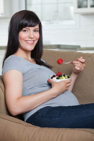 Portrait of pregnant woman eating fruit salad while sitting in sofa photo