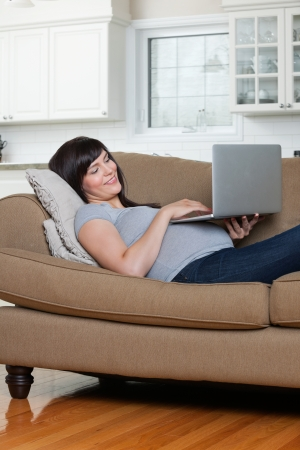 Happy pregnant woman using laptop while lying on sofa Stock Photo - 15450080
