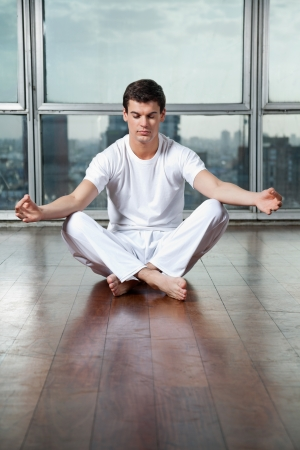 Full length of a young man meditating in lotus position at gym photo