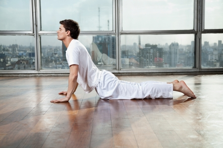 Side view of a young man doing Upward Facing Dog pose at gym photo