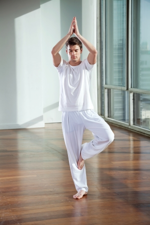 tree position: Full length of a young man standing in Tree Pose at gym Stock Photo