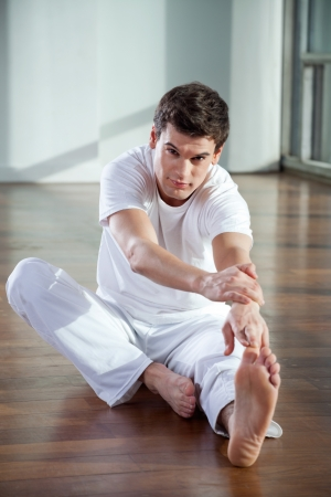 Portrait of a young man stretching his leg muscles at gym photo