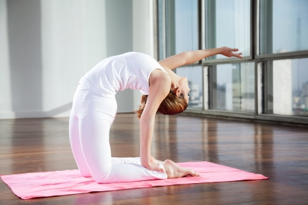 yoga mat: Full length of a young woman practicing yoga in Camel position on mat